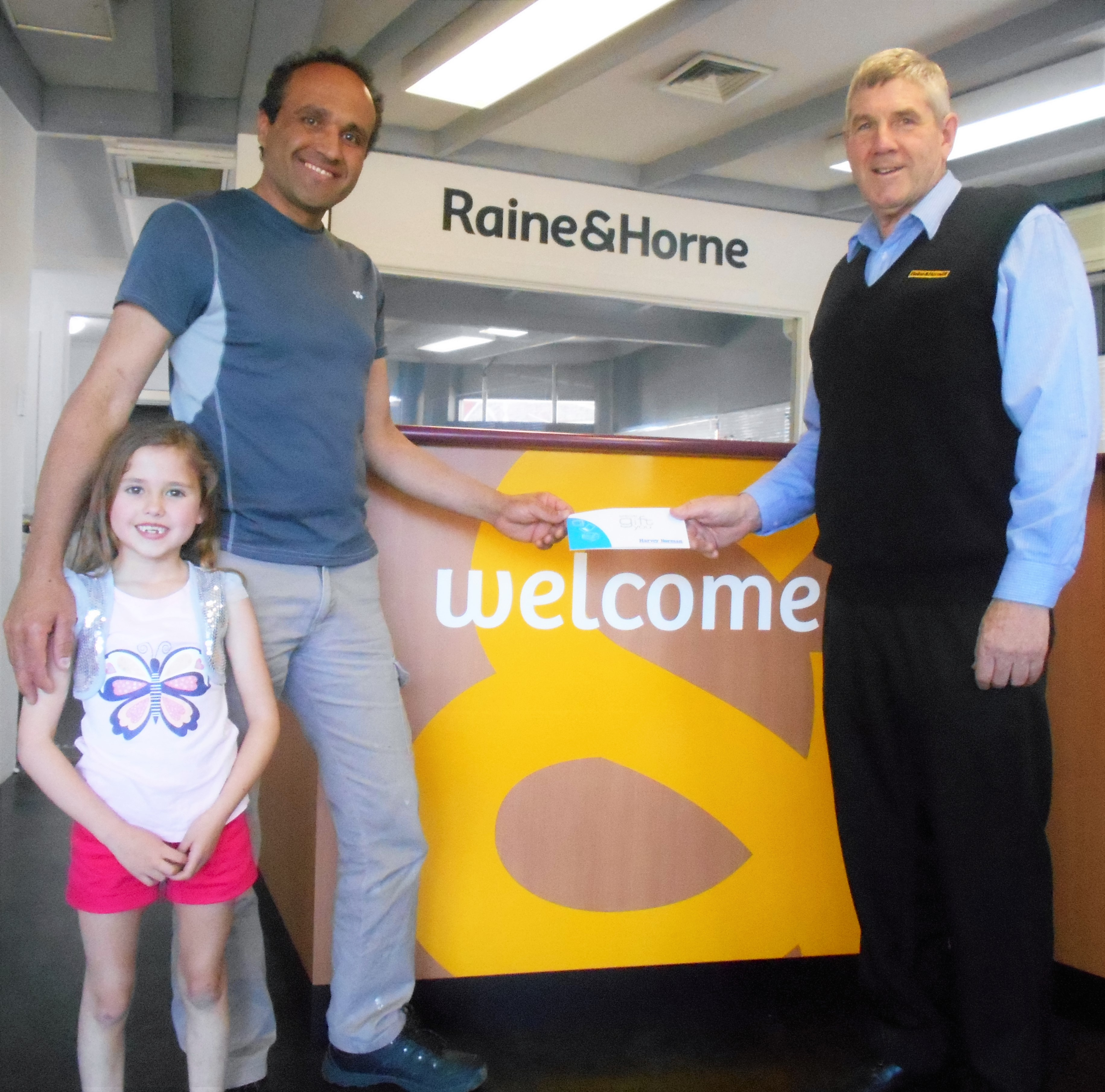 Mustapha Awik and daughter Rasha accepting the winning voucher from RH Young principal Graeme Schneider